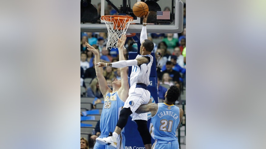 Dallas Mavericks guard Monta Ellis (11) shoots between Denver Nuggets defenders Timofey Mozgov (25) of Russia and Wilson Chandler (21) during the first half an NBA basketball game Friday, March 21, 2014, in Dallas. (AP Photo/LM Otero)