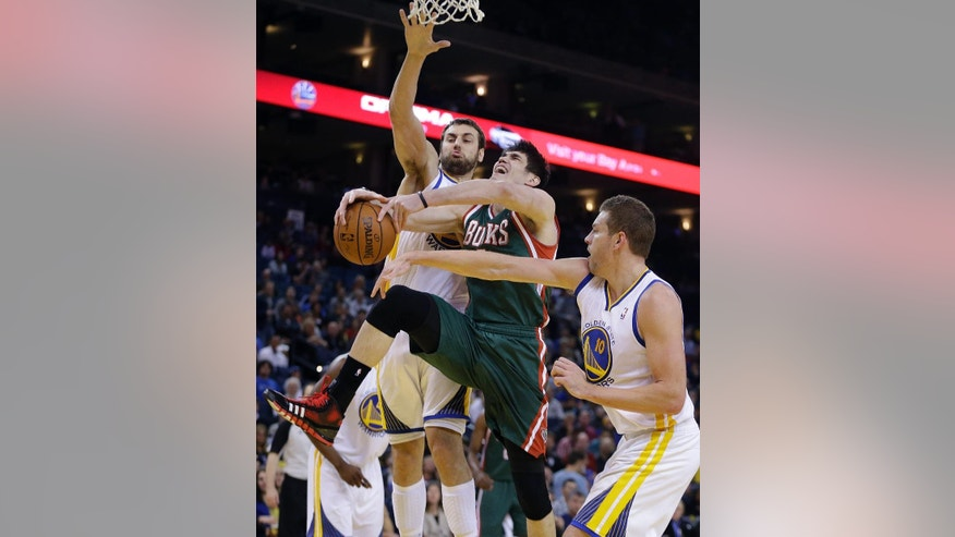 Milwaukee Bucks' Ersan Ilyasova, center, attempts to shoot between Golden State Warriors' Andrew Bogut, left, and David Lee during the first half of an NBA basketball game Thursday, March 20, 2014, in Oakland, Calif. (AP Photo/Ben Margot)