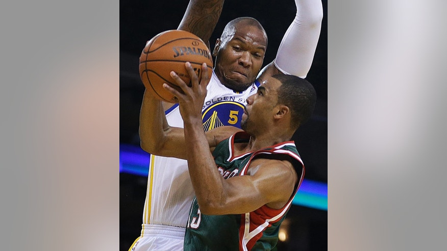 Milwaukee Bucks' Ramon Sessions shoots against Golden State Warriors' Marreese Speights (5) during the first half of an NBA basketball game Thursday, March 20, 2014, in Oakland, Calif. (AP Photo/Ben Margot)
