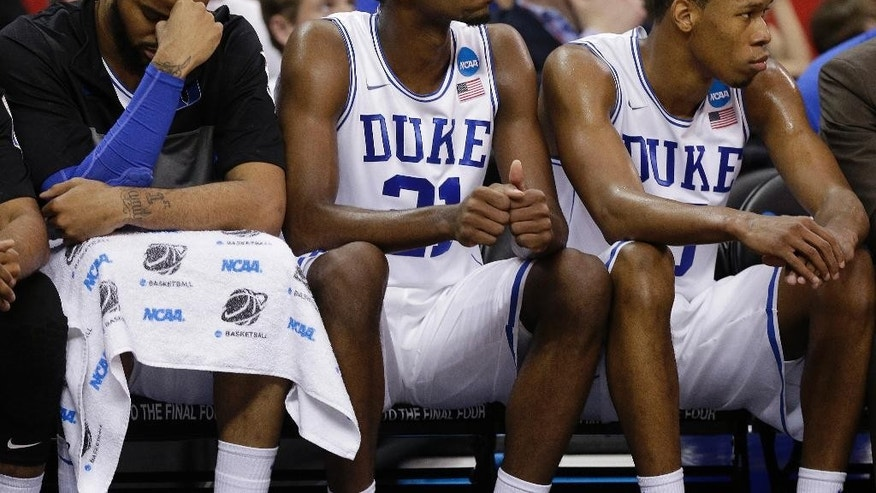 Duke's Josh Hairston, Amile Jefferson and Rodney Hood sit on the bench during the second half of an NCAA college basketball second-round game against Mercer, Friday, March 21, 2014, in Raleigh, N.C. Mercer won 78-71. (AP Photo/Chuck Burton)
