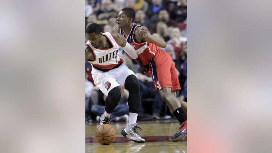 Washington Wizards guard Bradley Beal, right, plays tight defense on Portland Trail Blazers guard Wesley Matthews during the first half of an NBA basketball game in Portland, Ore., Thursday, March 20, 2014. (AP Photo/Don Ryan)