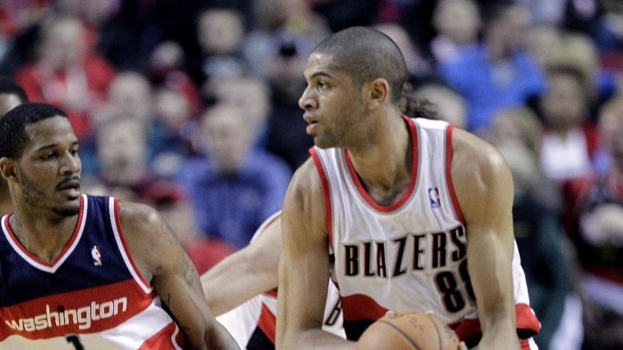 Portland Trail Blazers forward Nicolas Batum, right, from France,  looks to pass as Washington Wizards forward Trevor Ariza defends during the first half of an NBA basketball game in Portland, Ore., Thursday, March 20, 2014. (AP Photo/Don Ryan)