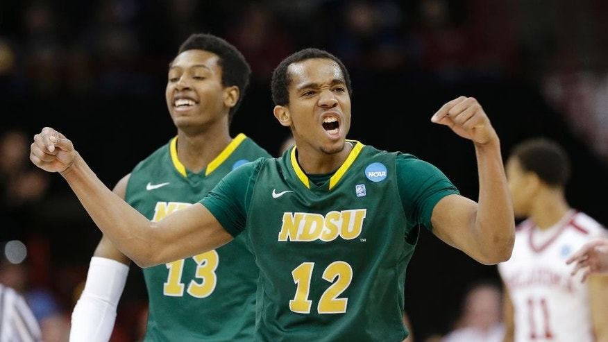 North Dakota State's Lawrence Alexander (12) celebrates in overtime during a second-round game against Oklahoma in the NCAA men's college basketball tournament in Spokane, Wash., Thursday, March 20, 2014. North Dakota State won 80-75. (AP Photo/Elaine Thompson)