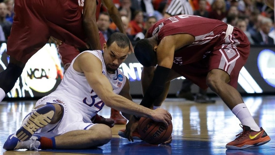 Kansas' Perry Ellis, left, and Eastern Kentucky's Corey Walden fight over a loose ball during the first half of a second-round game in the NCAA college basketball tournament Friday, March 21, 2014, in St. Louis. (AP Photo/Jeff Roberson)