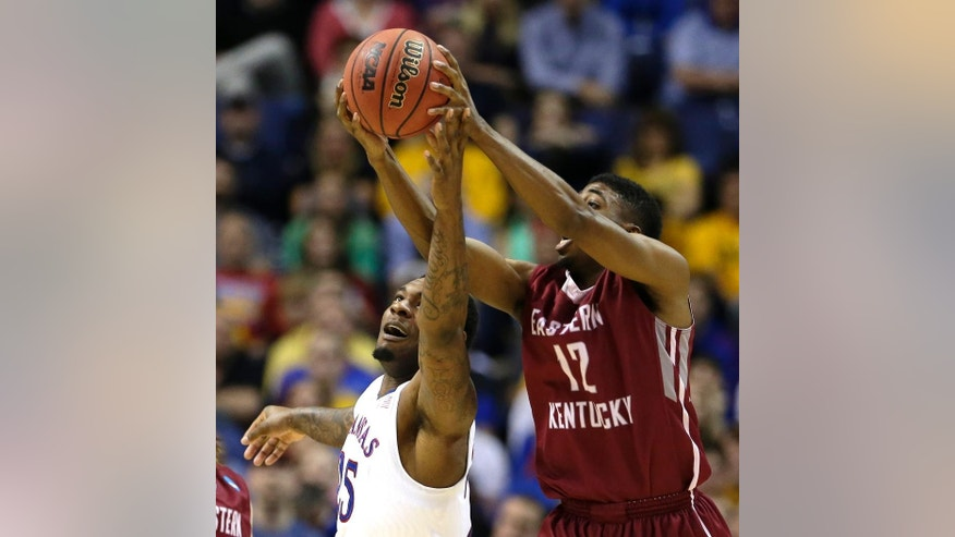 Kansas' Tarik Black, left, and Eastern Kentucky's Marcus Lewis (12) chase a loose ball during the second half of a second-round game in the NCAA college basketball tournament, Friday, March 21, 2014, in St. Louis. Kansas won the game 80-69. (AP Photo/Charlie Riedel)