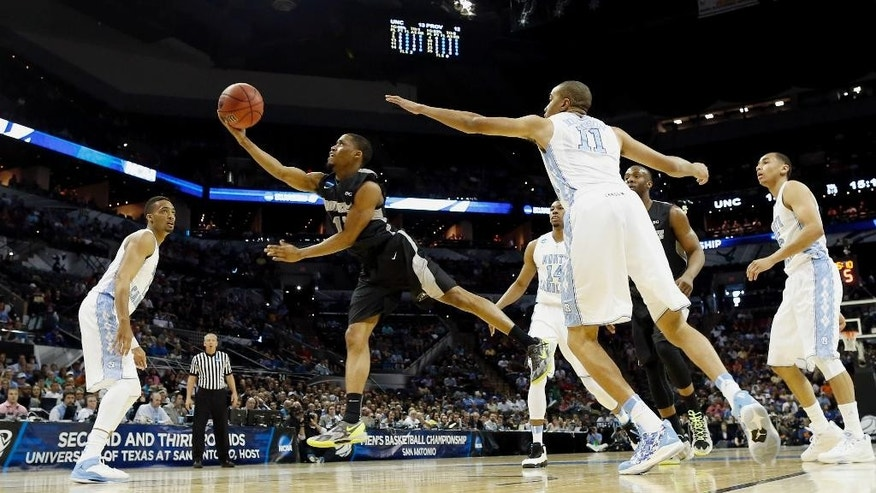 Providence's Bryce Cotton, left, goes up for a shot as North Carolina's Brice Johnson, right, defends during the first half of a second-round game in the NCAA college basketball tournament Friday, March 21, 2014, in San Antonio. (AP Photo/David J. Phillip)