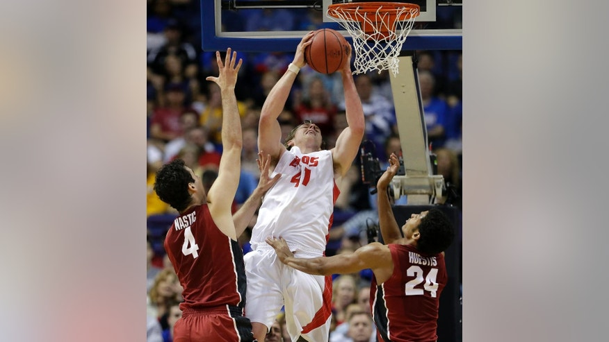New Mexico's Cameron Bairstow (41) grabs a rebound between Stanford's Stefan Nastic (4) and Josh Huestis (24) during the first half of a second-round game in the NCAA college basketball tournament, Friday, March 21, 2014, in St. Louis. (AP Photo/Charlie Riedel)