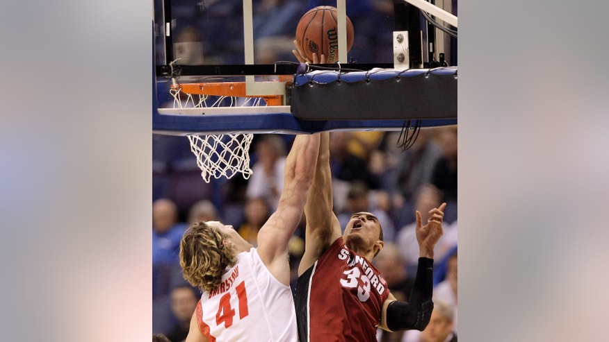New Mexico's Cameron Bairstow (41) blocks a shot by Stanford's Dwight Powell (33) during the first half of a second-round game in the NCAA college basketball tournament, Friday, March 21, 2014, in St. Louis. (AP Photo/Charlie Riedel)