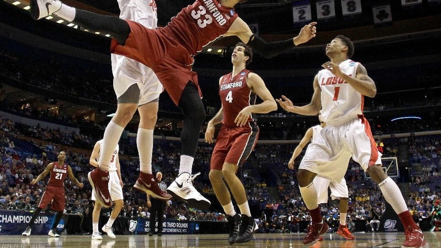New Mexico's Cameron Bairstow, left, blocks a shot by Stanford's Dwight Powell (33) during the first half of a second-round game in the NCAA college basketball tournament, Friday, March 21, 2014, in St. Louis. (AP Photo/Charlie Riedel)