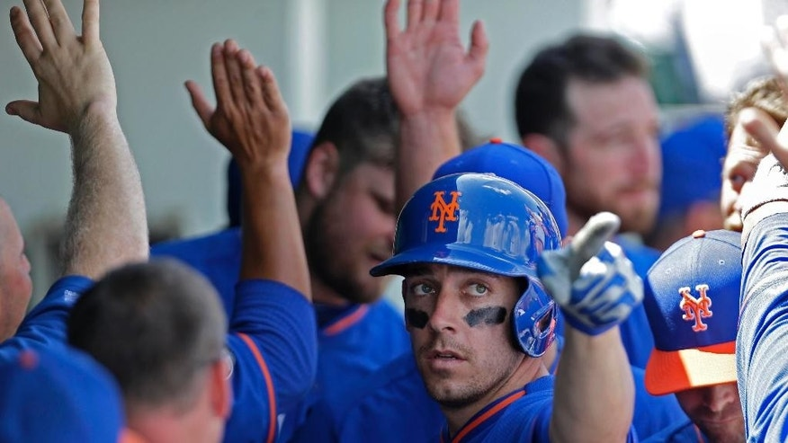 New York Mets' Taylor Teagarden points to teammates as he is congratulated in the dugout after his two-run homer in the first inning of a exhibition baseball game against the Minnesota Twins in Fort Myers, Fla., Friday, March 21, 2014. (AP Photo/Gerald Herbert)