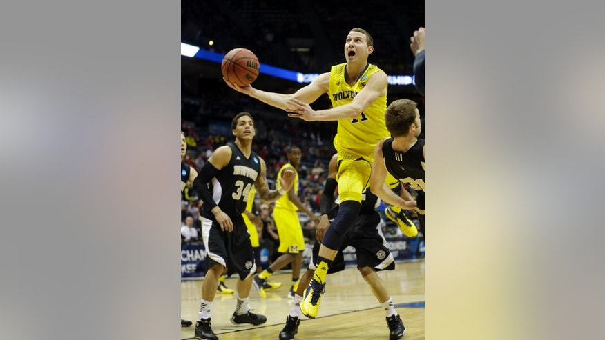 Michigan guard Nik Stauskas (11) goes to the basket against Wofford during the first half of a second round NCAA college basketball tournament game Thursday, March 20, 2014, in Milwaukee. (AP Photo/Morry Gash)