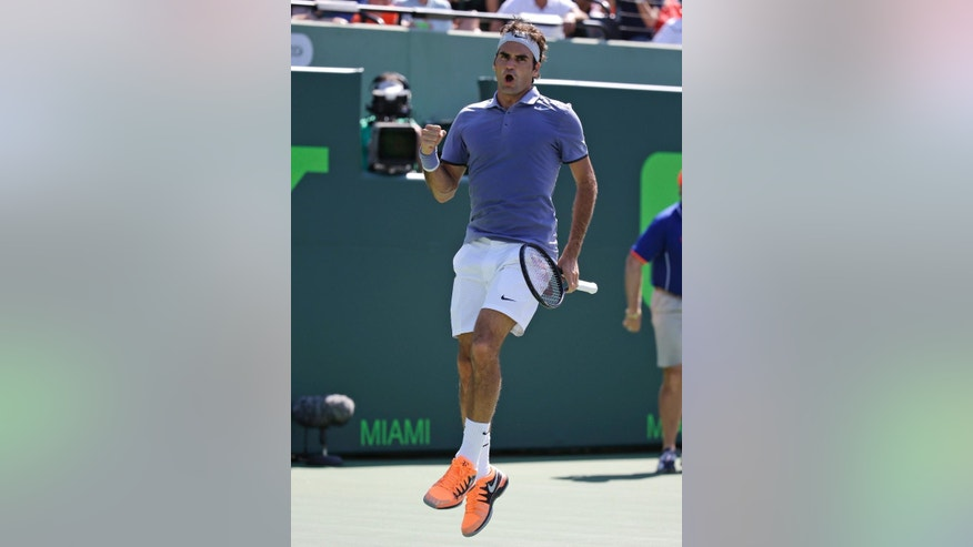 Roger Federer, of Switzerland, leaps into the air after defeating Ivo Karlovic, of Croatia,  6-4, 7-6 (7-4) at the Sony Open tennis tournament, Friday, March 21, 2014, in Key Biscayne, Fla. (AP Photo/Lynne Sladky)