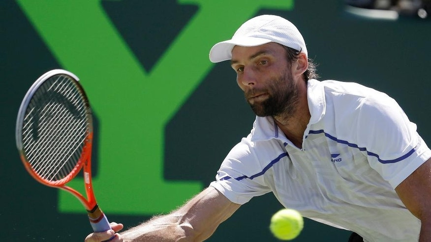 Ivo Karlovic, of Croatia, returns the ball to Roger Federer, of Switzerland, during a match at the Sony Open tennis tournament, Friday, March 21, 2014, in Key Biscayne, Fla. (AP Photo/Lynne Sladky)