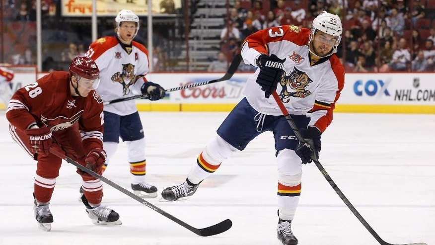 Florida Panthers' Brandon Pirri (73) gets ready to pass the puck as Phoenix Coyotes' Lauri Korpikoski (28), of Finland, closes in and Panthers' Brian Campbell (51) watches during the first period of an NHL hockey game, Thursday, March 20, 2014, in Glendale, Ariz. (AP Photo/Ross D. Franklin)
