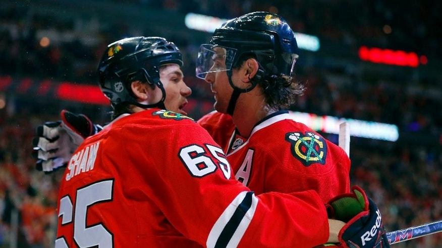 Chicago Blackhawks center Andrew Shaw (65) celebrates with left wing Patrick Sharp (10) after Sharp scored a goal against the Carolina Hurricanes during the second period of an NHL hockey game in Chicago, Friday, March 21, 2014. (AP Photo/Jeff Haynes)