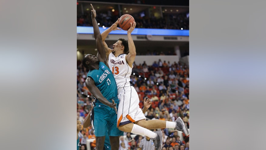 Virginia forward Anthony Gill (13) shoots over Coastal Carolina center El Hadji Ndieguene (11) during the first half of an NCAA college basketball second-round tournament game, Friday, March 21, 2014, in Raleigh. (AP Photo/Gerry Broome)