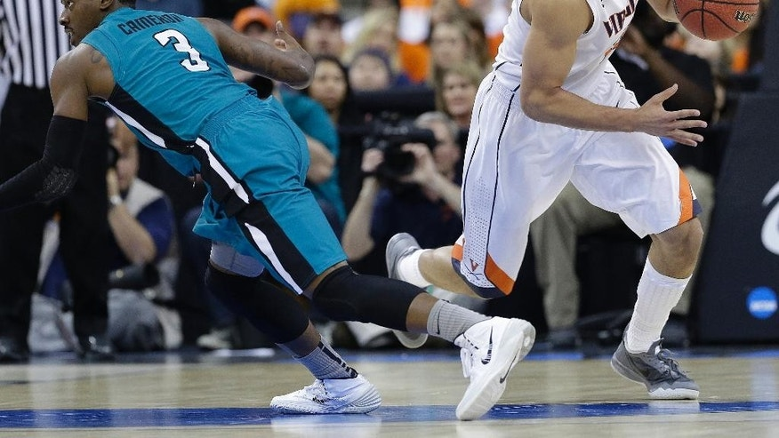 Virginia forward Anthony Gill (13) picks up a loose ball from Coastal Carolina guard Josh Cameron (3) during the first half of an NCAA college basketball second-round tournament game, Friday, March 21, 2014, in Raleigh. (AP Photo/Gerry Broome)