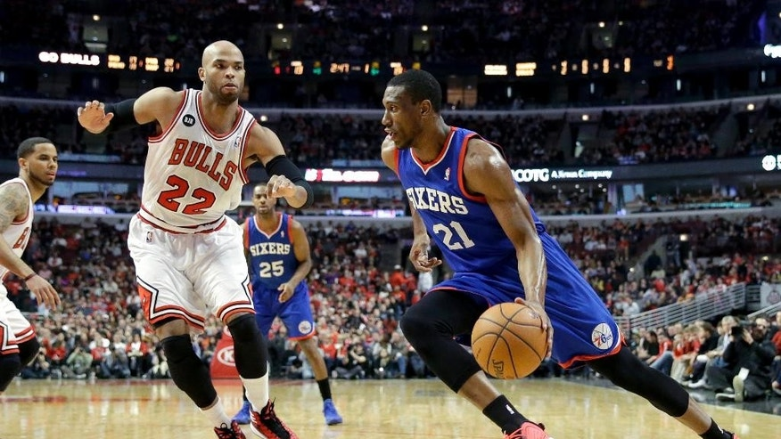 Philadelphia 76ers forward Thaddeus Young (21), right, drives as Chicago Bulls forward Taj Gibson (22) guards during the first half of an NBA basketball game in Chicago on Saturday, March 22, 2014. (AP Photo/Nam Y. Huh)