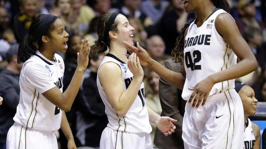 Purdue forward Camille Redmon, right, celebrates with teammates guard April Wilson. left, and guard Courtney Moses as she leaves the game during the second half of a first-round game against Akron in the NCAA women's college basketball tournament in West Lafayette, Ind., Saturday, March 22, 2014. Purdue defeated Akron 84-55. (AP Photo/Michael Conroy)