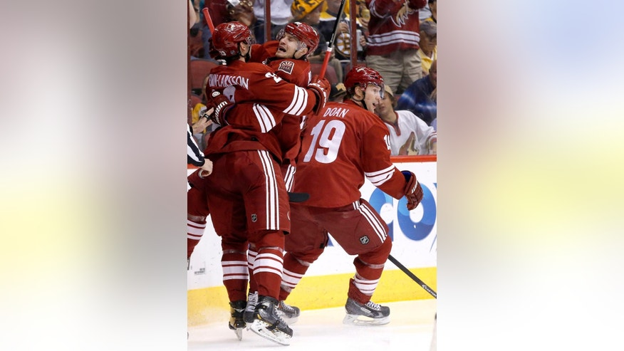 Phoenix Coyotes' Oliver Ekman-Larsson, left, of Sweden, celebrates his goal against the Boston Bruins with teammates Mikkel Boedker, of Denmark, and Shane Doan (19) during the second period of an NHL hockey game on Saturday, March 22, 2014, in Glendale, Ariz. (AP Photo/Ross D. Franklin)