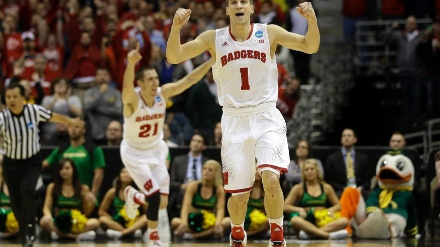 Wisconsin guards Ben Brust (1) and Josh Gasser (21) react to a foul call against Oregon during the second half of a third-round game of the NCAA college basketball tournament Saturday, March 22, 2014, in Milwaukee. Wisconsin won 82-77. (AP Photo/Morry Gash)