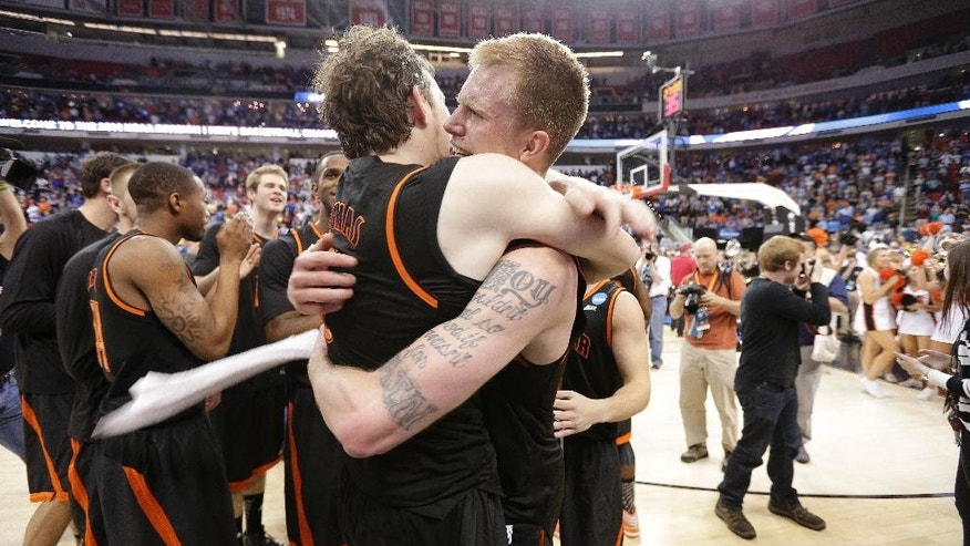 Mercer'sJakob Gollon, right, and Bud Thomas embrace after defeating Duke 78-71 in an NCAA college basketball second-round game against Duke, Friday, March 21, 2014, in Raleigh, N.C.  (AP Photo/Chuck Burton)