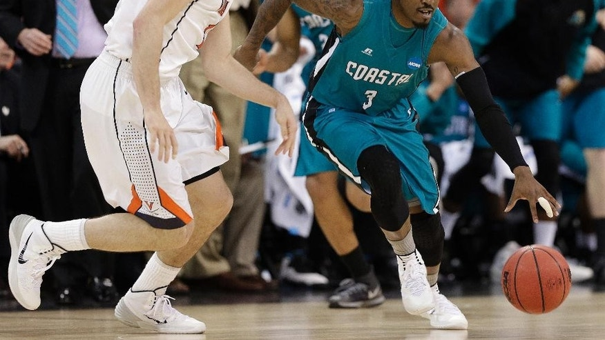 Coastal Carolina guard Josh Cameron (3) moves the ball against Virginia guard Joe Harris (12) during the first half of an NCAA college basketball second-round tournament game, Friday, March 21, 2014, in Raleigh. (AP Photo/Chuck Burton)