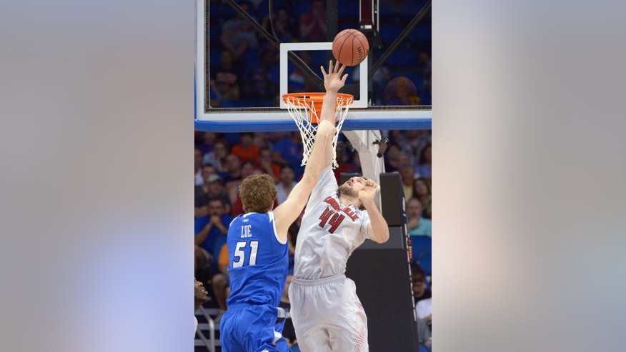 Saint Louis forward Rob Loe (51) shoots over Louisville forward Stephan Van Treese (44)  during the second half in a third-round game in the NCAA college basketball tournament  Saturday, March 22, 2014, in Orlando, Fla. (AP Photo/Phelan M. Ebenhack)