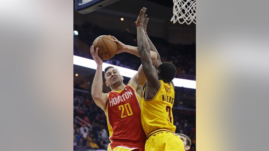 Houston Rockets' Donatas Motiejunas (20), from Lithuania, shoots over Cleveland Cavaliers' Dion Waiters (3) during an NBA basketball game, Saturday, March 22, 2014, in Cleveland. (AP Photo/Tony Dejak)