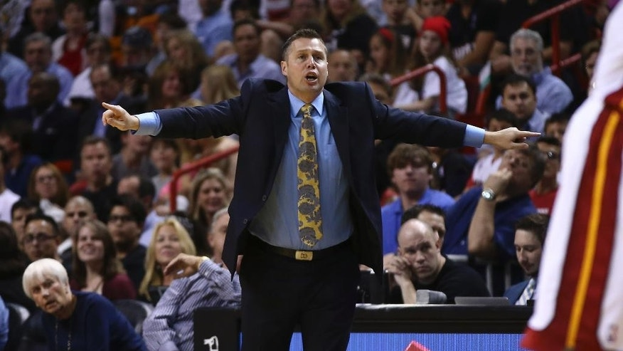 Memphis Grizzlies coach David Joerger yells instructions to his team during the first half of an NBA basketball game in Miami, Friday, March 21, 2014, against the Miami Heat. (AP Photo/J Pat Carter)