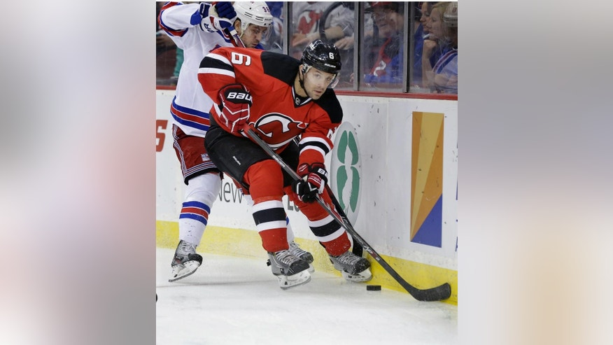 New Jersey Devils' Andy Greene (6) keeps the puck away from New York Rangers' Mats Zuccarello, of Norway, during the first period of an NHL hockey game game Saturday, March 22, 2014, in Newark, N.J. (AP Photo/Mel Evans)