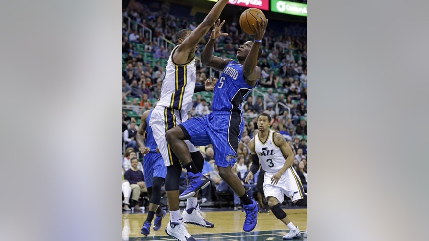 Utah Jazz's Derrick Favors, left, defends against Orlando Magic's Victor Oladipo (5) who goes to the basket as Utah Jazz's Trey Burke (3) looks on in the first quarter during an NBA basketball game on Saturday, March 22, 2014, in Salt Lake City. (AP Photo/Rick Bowmer)