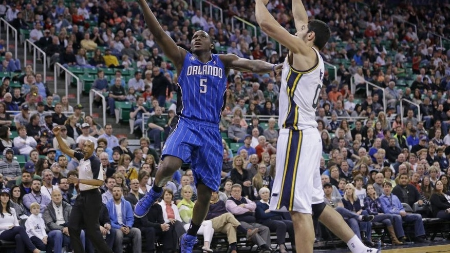 Orlando Magic's Victor Oladipo (5) goes to the basket as Utah Jazz's Enes Kanter (0), of Turkey, defends in the second quarter during an NBA basketball game on Saturday, March 22, 2014, in Salt Lake City. (AP Photo/Rick Bowmer)