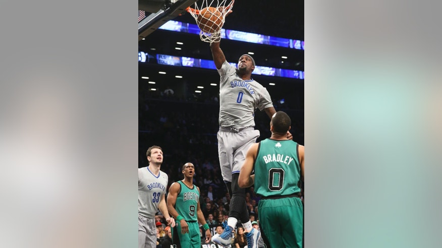 Brooklyn Nets center Andray Blatche (0) dunks as forward Mirza Teletovic (33), Boston Celtics guard Rajon Rondo (9), and guard Avery Bradley (0) look on during the first half of an NBA basketball game at the Barclays Center, Friday, March 21, 2014, in New York. (AP Photo/John Minchillo)