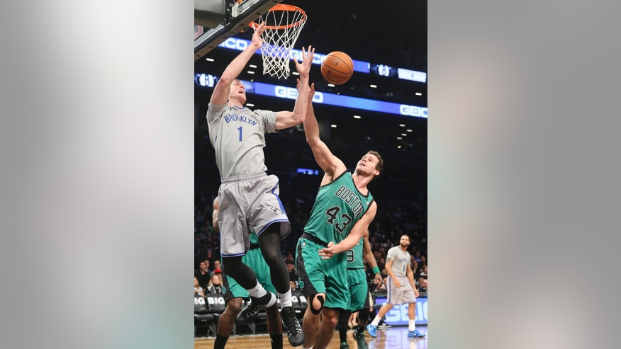 Boston Celtics center Kris Humphries (43) fouls Brooklyn Nets forward Mason Plumlee (1) during the first half of an NBA basketball game at the Barclays Center, Friday, March 21, 2014, in New York. (AP Photo/John Minchillo)