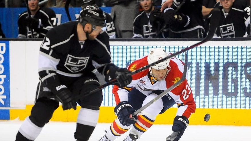 Florida Panthers center Scott Gomez (23) attempts to grab the puck as Los Angeles Kings right wing Marian Gaborik (12), of Slovakia, looks on during the second period of an NHL hockey game on Saturday, March 22, 2014, in Los Angeles. (AP Photo/Gus Ruelas)