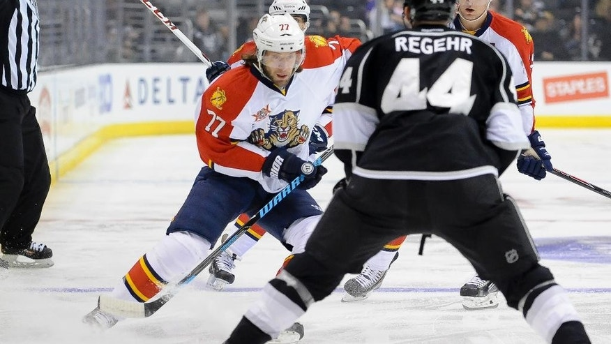 Florida Panthers defenseman Tom Gilbert (77) brings the puck upice as he attempts get by Los Angeles Kings defenseman Robyn Regehr (44), of Brazil, during the first period of an NHL hockey game on Saturday, March 22, 2014, in Los Angeles. (AP Photo/Gus Ruelas)