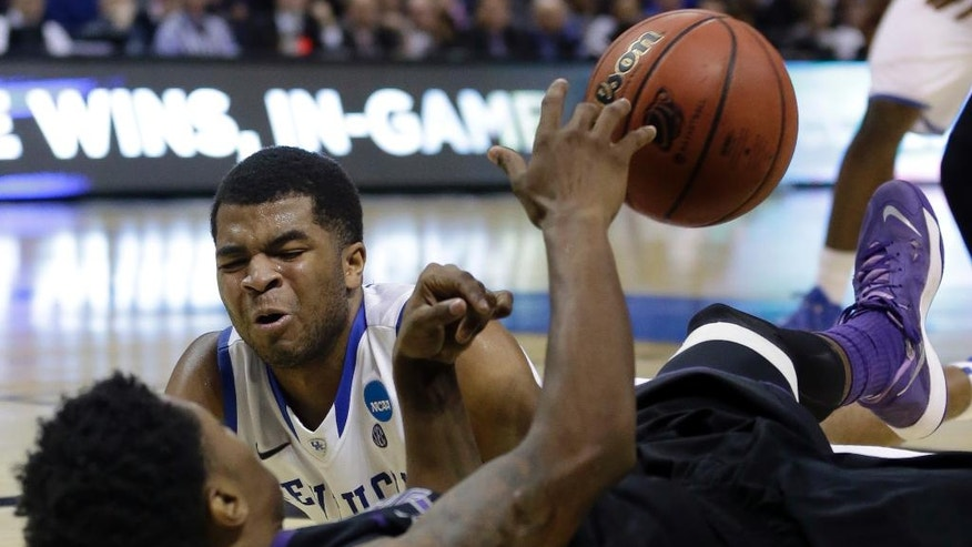 Kansas State's Nigel Johnson, front, and Kentucky's Andrew Harrison scramble after a loose ball during the second half of a second-round game in the NCAA college basketball tournament Friday, March 21, 2014, in St. Louis. (AP Photo/Jeff Roberson)
