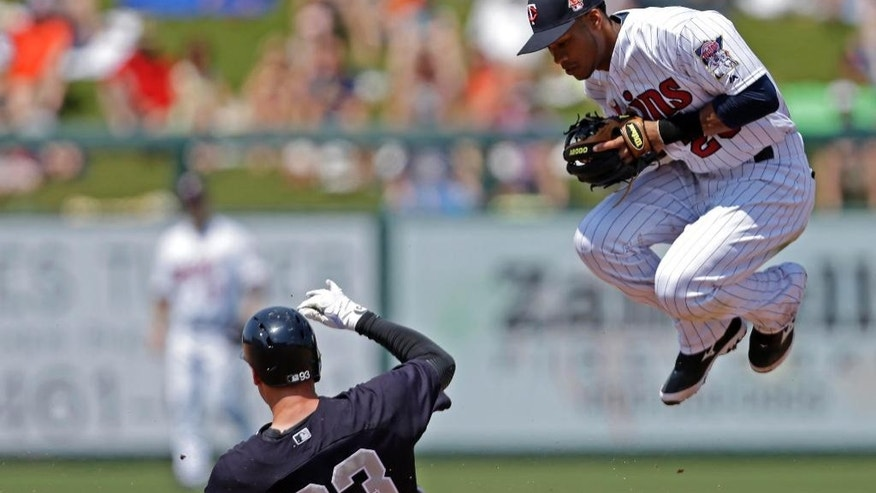 Minnesota Twins shortstop Pedro Florimon leaps out of the was a New York Yankees Dean Anna (93) is forced out at second on a grounder off the bat of Zoilo Almonte in the fourth inning of an exhibition baseball game in Fort Myers, Fla., Saturday, March 22, 2014. (AP Photo/Gerald Herbert)