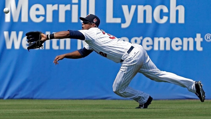 Minnesota Twins center fielder Aaron Hicks dives to grab a fly out by New York Yankees  Kelly Johnson to end the fifth inning of an exhibition baseball game in Fort Myers, Fla., Saturday, March 22, 2014. (AP Photo/Gerald Herbert)