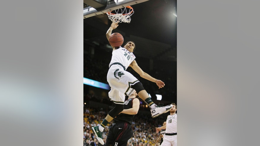 Michigan State's Travis Trice (20) dunks in the first half during the third-round game of the NCAA men's college basketball tournament against Harvard in Spokane, Wash., Saturday, March 22, 2014. (AP Photo/Young Kwak)