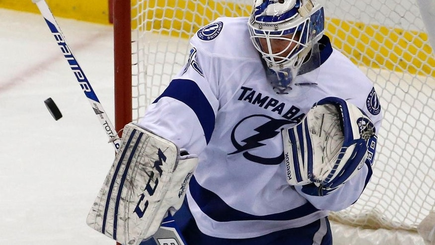 Tampa Bay Lightning goalie Anders Lindback (39) stops a shot in the first period of an NHL hockey game between the Pittsburgh Penguins and the Tampa Bay Lightning in Pittsburgh, Saturday, March 22, 2014. (AP Photo/Gene J. Puskar)