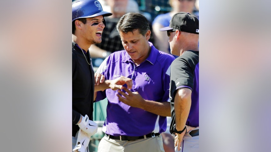 Colorado Rockies' Nolan Arenado, left, is check head trainer Keith Dugger and bench coach Tom Runnells (11) after being hit in the hand by a pitch from Cleveland Indians starting pitcher Corey Kluber in the sixth inning of a spring exhibition baseball game Saturday, March 22, 2014, in Goodyear, Ariz. Arenado left the game after the injury. (AP Photo/Mark Duncan)