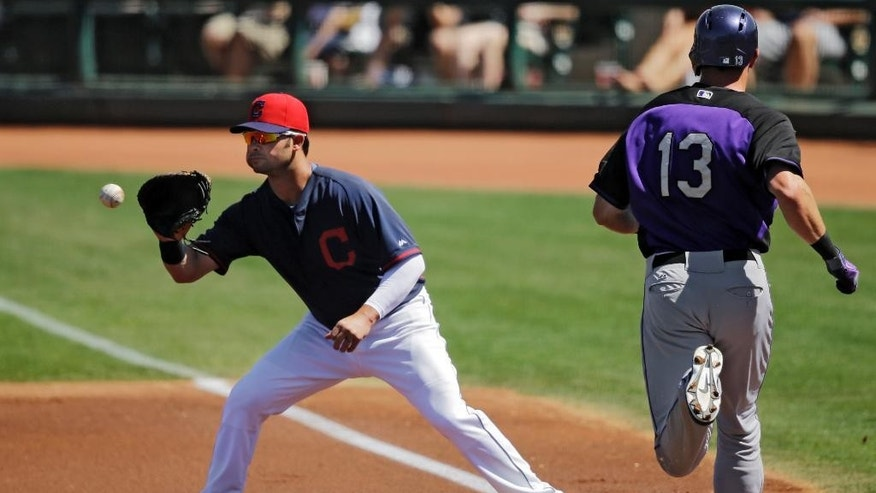 Cleveland Indians first baseman Nick Swisher takes the throw at first to get Colorado Rockies' Drew Stubbs (13) on a ground out in the first inning of a spring exhibition baseball game, Saturday, March 22, 2014, in Goodyear, Ariz. (AP Photo/Mark Duncan)