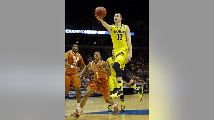 Michigan guard Nik Stauskas (11) drives to the basket during the first half of a third-round game against the Texas of the NCAA college basketball tournament Saturday, March 22, 2014, in Milwaukee. (AP Photo/Morry Gash)