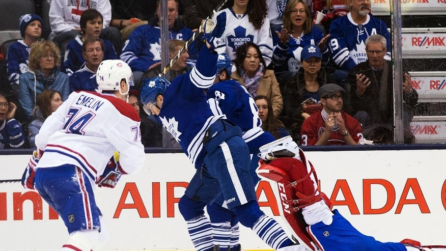 Toronto Maple Leafs forward James van Riemsdyk, center, gets called for an interference penalty after taking out Montreal Canadiens goalie Carey Price, right, during the third period of an NHL hockey game in Toronto on Saturday, March 22, 2014. (AP Photo/The Canadian Press, Nathan Denette)
