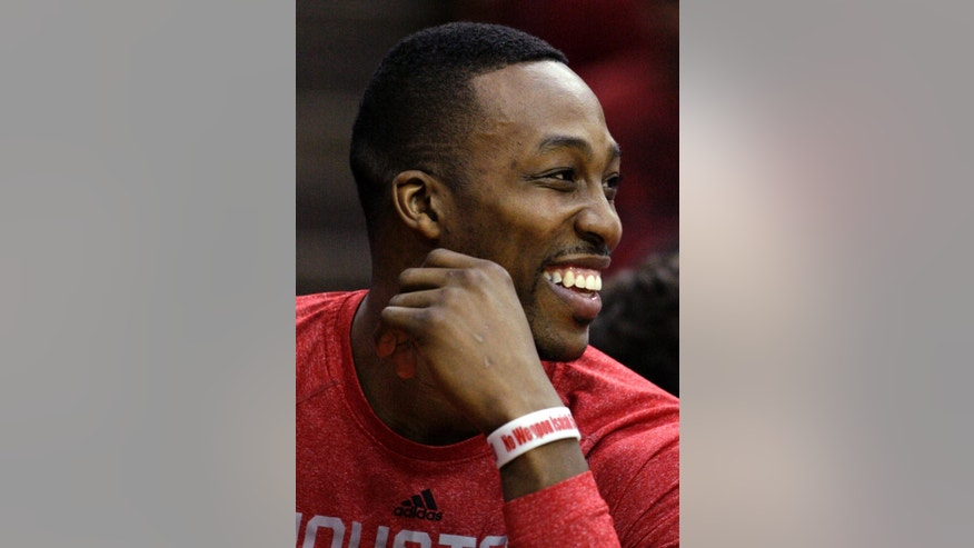 Houston Rockets guard Dwight Howard smiles as he watches the fourth quarter of an NBA basketball game against the Minnesota Timberwolves, Thursday, March 20, 2014, in Houston. The Rockets defeated the Timberwolves 129-106. (AP Photo/Patric Schneider)