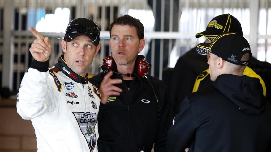 Driver Matt Kenseth, left, talks with his crew in his garage after practice for the NASCAR Sprint Cup series auto race in Fontana, Calif., Saturday, March 22, 2014.(AP Photo/Alex Gallardo)