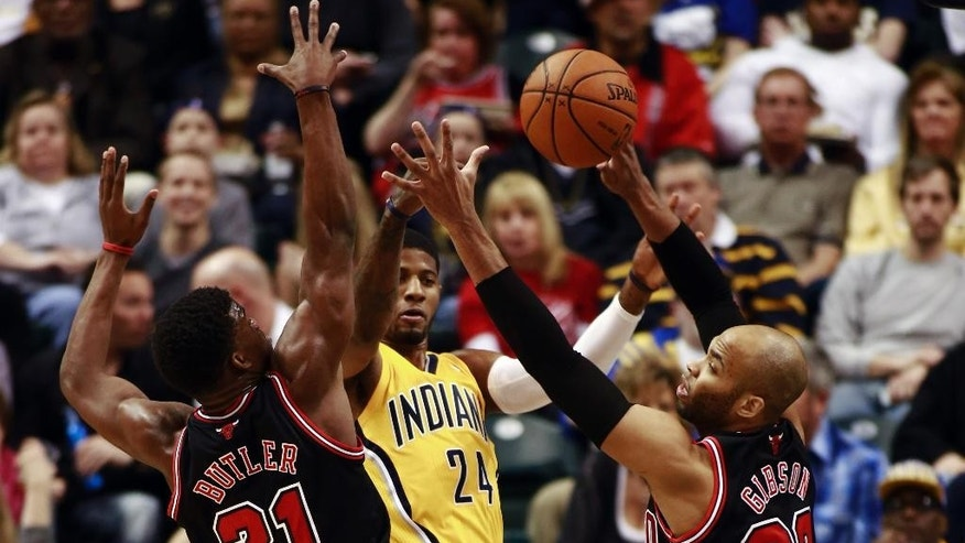 Indiana Pacers forward Paul George (24) passes the basketball between Chicago Bulls guard Jimmy Butler (21) and forward Taj Gibson during the first half of an NBA basketball game in Indianapolis, Friday, March 21, 2014. (AP Photo/R Brent Smith)