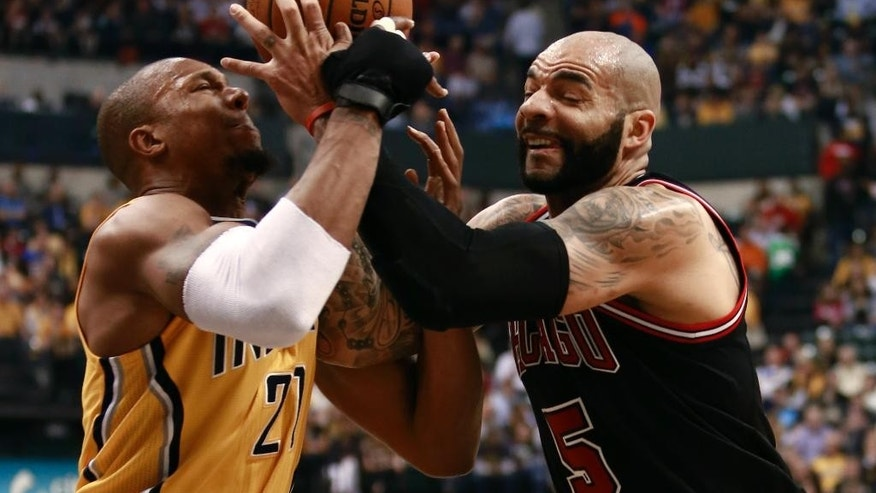 CORRECTS SPELLING OF BOOZER - Chicago Bulls forward Carlos Boozer, right, competes with Indiana Pacers forward David West for the basketball in the first half of an NBA basketball game in Indianapolis, Friday, March 21, 2014. (AP Photo/R Brent Smith)